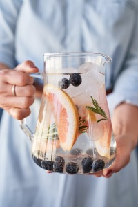woman holding jug of fruit herb infused iced water, healthy flavoured grapefruit infusion party drink refreshment